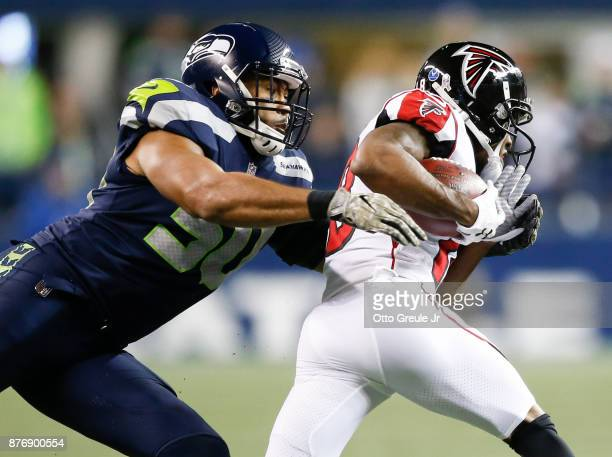 Linebacker KJ Wright of the Seattle Seahawks tackles wide receiver Taylor Gabriel of the Atlanta Falcons during the third quarter of the game at...