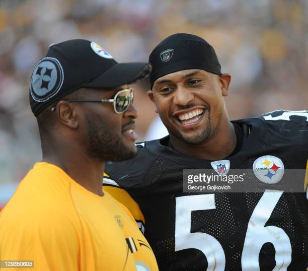 Linebacker LaMarr Woodley of the Pittsburgh Steelers talks with injured teammate James Harrison on the sideline during a game against the Tennessee...