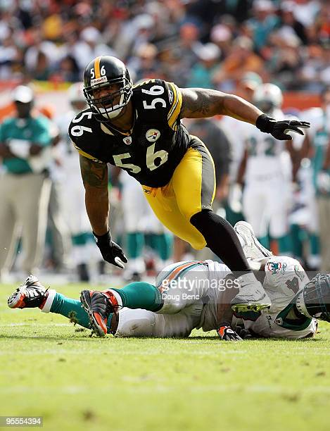 Linebacker LaMarr Woodley of the Pittsburgh Steelers tries to get into the backfield after running over running back Ricky Williams of the Miami...
