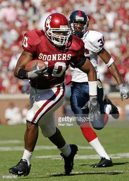 Linebacker Lance Mitchell of the Oklahoma Sooners takes off for a 28yard touchdown while being pursued by fullback Russell Dennison of the Kansas...