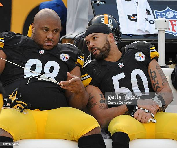 Linebacker Larry Foote of the Pittsburgh Steelers talks to defensive lineman Casey Hampton as Hampton removes tape from his fingers as they sit on...
