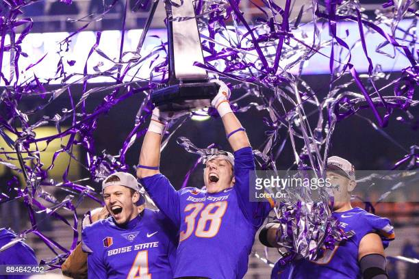 Linebacker Leighton Vander Esch and quarterback Brett Rypien of the Boise State Broncos hoist the championship trophy at the conclusion of the...