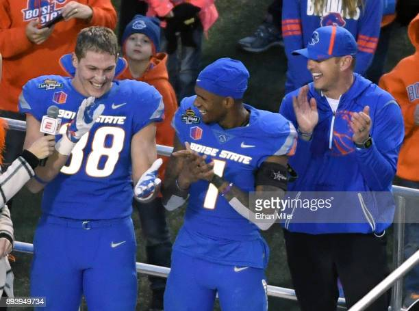 Linebacker Leighton Vander Esch and wide receiver Cedrick Wilson of the Boise State Broncos celebrate with head coach Bryan Harsin after the team...