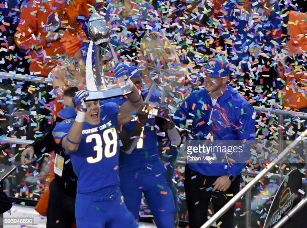 Linebacker Leighton Vander Esch of the Boise State Broncos holds up the championshop trophy as he celebrates with head coach Bryan Harsin after the...