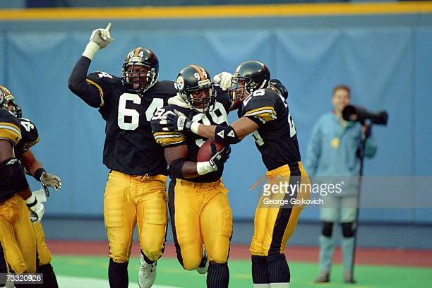Linebacker Levon Kirkland of the Pittsburgh Steelers is congratulated by defensive lineman Kenny Davidson and defensive back Rod Woodson after...