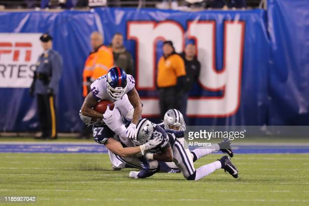 Linebacker Luke Gifford and Safety Xavier Woods of the Dallas Cowboys make a stop against the New York Giants in the first half at MetLife Stadium on...