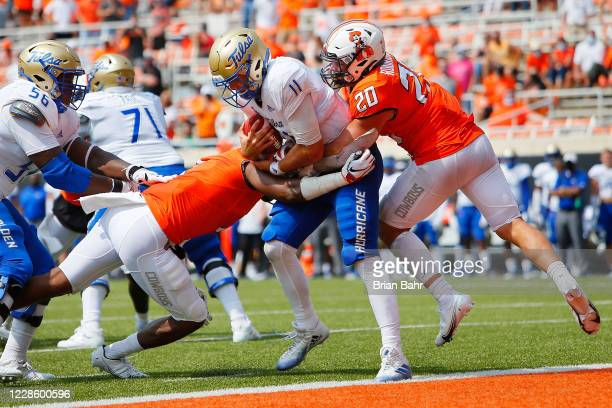 Linebacker Malcolm Rodriguez and linebacker Calvin Bundage of the Oklahoma State Cowboys sack quarterback Zach Smith of the Tulsa Golden Hurricanes...