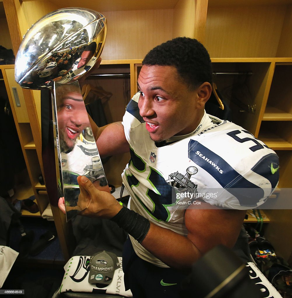 Linebacker Malcolm Smith #53 of the Seattle Seahawks celebrates with the Vince Lombardi Trophy after in the locker room after the 43-8 victory over the Denver Broncos during Super Bowl XLVIII at MetLife Stadium on February 2, 2014 in East Rutherford, New Jersey.