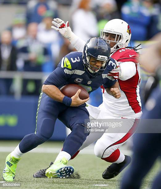 Linebacker Markus Golden of the Arizona Cardinals takes down quarterback Russell Wilson of the Seattle Seahawks at CenturyLink Field on December 24...