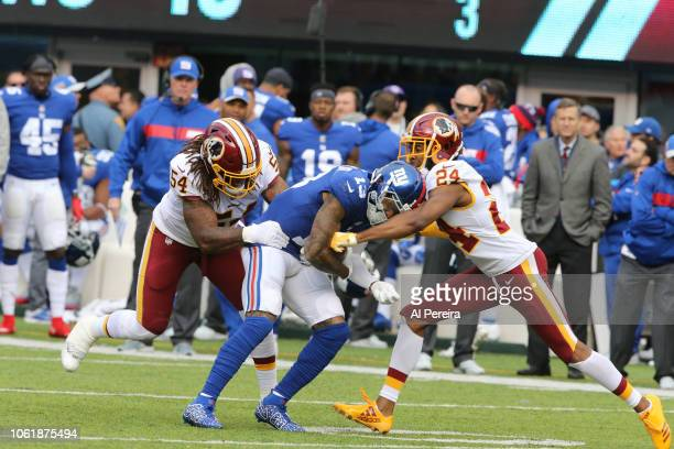 Linebacker Mason Foster and Cornerback Josh Norman of the Washington Redskins make a stop against the New York Giants during their game at MetLife...