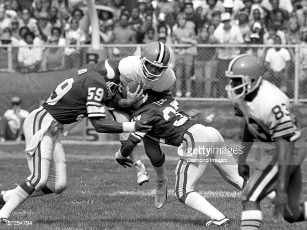 Linebacker Matt Blair and defensive back Willie Teal of the Minnesota Vikings tackle quarterback Brian Sipe of the Cleveland Browns during a game on...