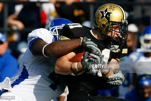 Linebacker Micah Johnson of the Kentucky Wildcats wraps up tailback Jared Hawkins of the Vanderbilt Commodores during the first half at Vanderbilt...