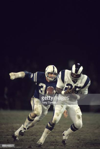 Linebacker Mike Curtis of the Baltimore Colts closes in to tackle runningback Travis Williams of the Los Angeles Rams as he drops a pass during a...