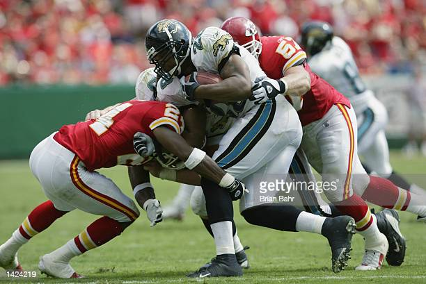 Linebacker Mike Maslowski and cornerback William Bartee of the Kansas City Chiefs tackle running back Fred Taylor of the Jacksonville Jaguars during...