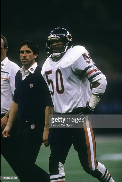Linebacker Mike Singletary of the Chicago Bears walking off the field with a team trainer and docter during Super Bowl XX January 26 1986 against the...