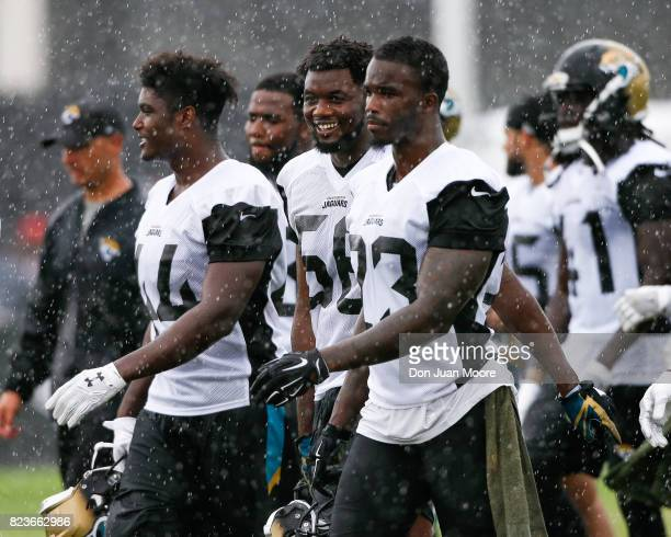 Linebacker Myles Jack Defensive End Dante Fowler Jr #56 and Safety James Sample of the Jacksonville Jaguars walks through the rain after Training...