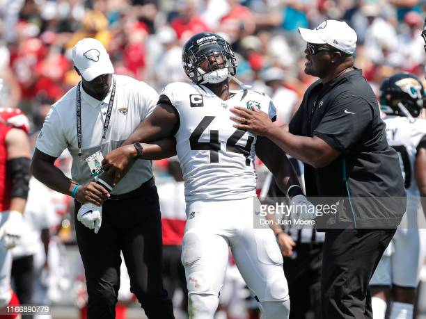 Linebacker Myles Jack of the Jacksonville Jaguars is taken off the field by team officials after being ejected for throwing a punch at Wide Receiver...