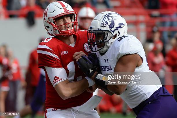 Linebacker Nate Hall of the Northwestern Wildcats hits quarterback Tanner Lee of the Nebraska Cornhuskers after a pass at Memorial Stadium on...
