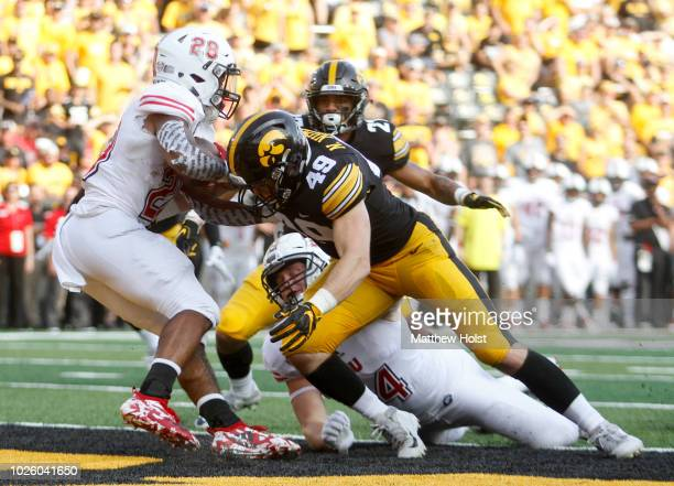 Linebacker Nick Niemann and defensive back Amani Hooker of the Iowa Hawkeyes stop tailback Jordan Nettles of the Northern Illinois Huskies for a...