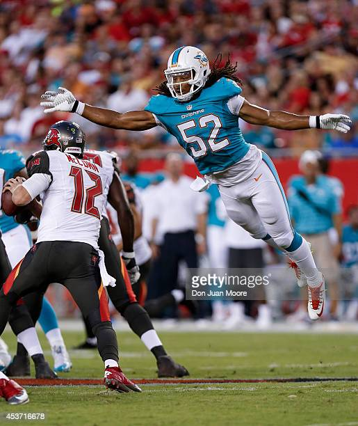 Linebacker Philip Wheeler of the Miami Dolphins leap at Quarterback Josh McCown#12 of the Tampa Bay Buccaneers to break up a play during the game at...