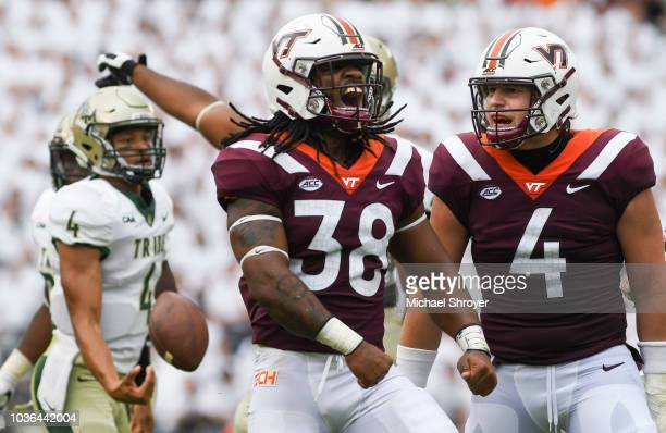 Linebacker Rico Kearney of the Virginia Tech Hokies reacts with linebacker Dax Hollifield following a play against the William Mary Tribe in the...