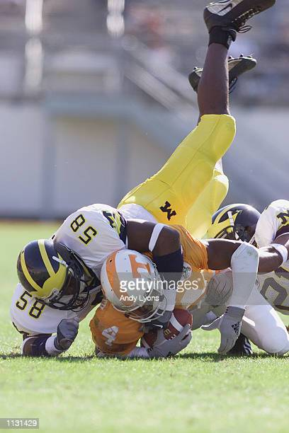 Linebacker Roy Manning of the Michigan Wolverines tackles wide receiver Donte' Stallworth of the Tennessee Volunteers during the Citrus Bowl on...