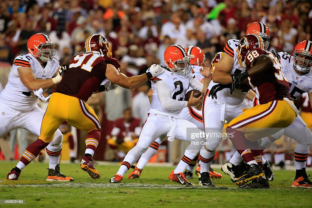 Linebacker Ryan Kerrigan #91 of the Washington Redskins tackles quarterback Johnny Manziel #2 of the Cleveland Browns during a preseason game at FedExField on August 18, 2014 in Landover, Maryland.