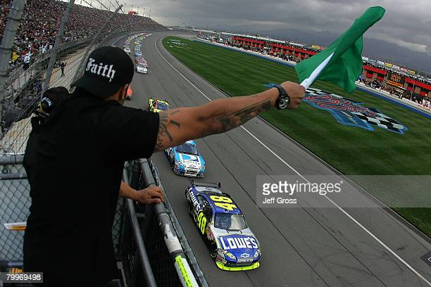 NFL linebacker Shawne Merriman waves the green flag as Jimmie Johnson driver of the Lowe's Chevrolet leads the field at the start of the NASCAR...