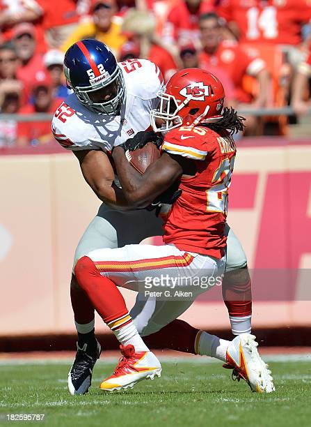 Linebacker Spencer Paysinger of the New York Giants tackles running back Jamaal Charles of the Kansas City Chiefs during the first half on September...