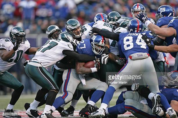 Linebacker Stewart Bradley and safety Quintin Mikell of the Philadelphia Eagles tackle running back Brandon Jacobs of the New York Giants during the...