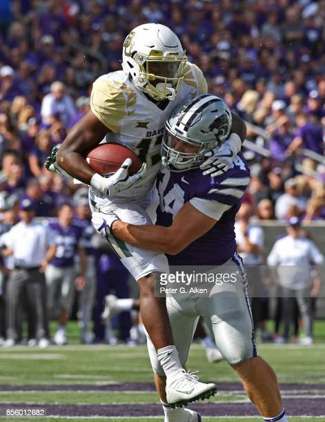 Linebacker Tanner Wood of the Kansas State Wildcats tackles wide receiver Tony Nicholson of the Baylor Bears during the first half on September 30...
