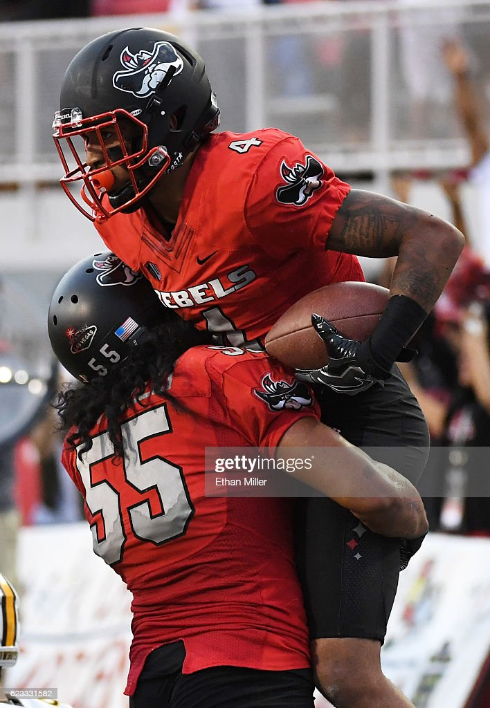 Linebacker Tau Lotulelei #55 of the UNLV Rebels lifts up defensive back Torry McTyer #4 after he intercepted a pass in the third overtime of their game against the Wyoming Cowboys at Sam Boyd Stadium on November 12, 2016 in Las Vegas, Nevada. UNLV won 69-66 in triple overtime.