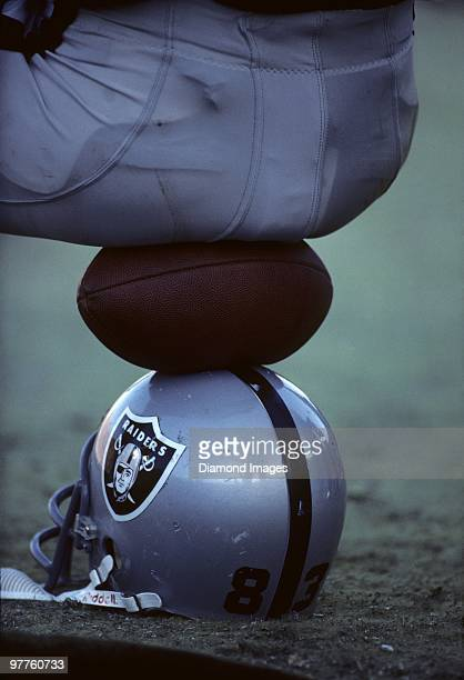Linebacker Ted Hendricks of the Los Angeles Raiders sits on a football on top of his helmet on the sidelines during the AFC Divisional Playoff Game...