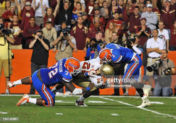 Linebacker Telvin Smith of the Florida State Seminoles breaks through a block of center Jonotthan Harrison to tackle running back Chris Rainey of the...
