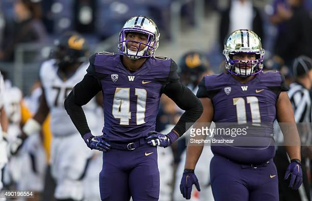 Linebacker Travis Feeney of the Washington Huskies and defensive lineman Elijah Qualls of the Washington Huskies walks off the field after losing to...