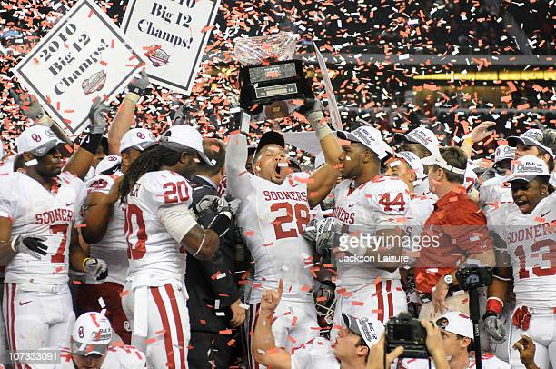 Linebacker Travis Lewis of the Oklahoma Sooners holds up the Big Twelve Championship trophy in in front of his teammates after beating the Nebraska...