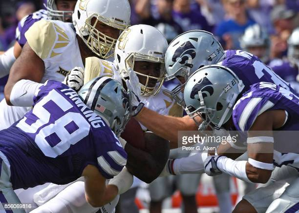 Linebacker Trent Tanking of the Kansas State Wildcats tackles running back Terence Williams of the Baylor Bears during the first half on September 30...