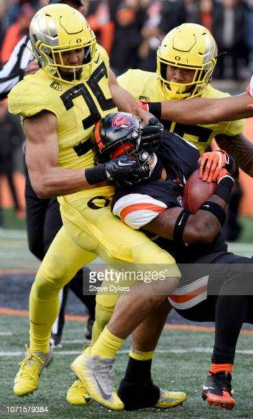 Linebacker Troy Dye of the Oregon Ducks is called for a face mask penalty as he tackles running back Jermar Jefferson of the Oregon State Beavers...