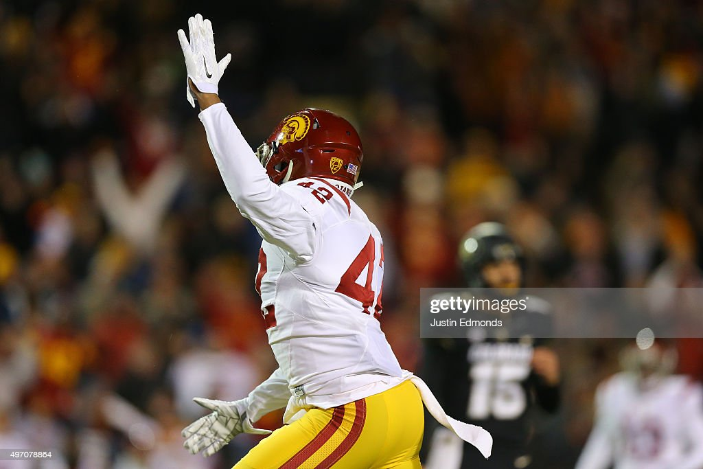 Linebacker Uchenna Nwosu #42 of the USC Trojans celebrates a fumble recovery by his team as quarterback Cade Apsay #15 of the Colorado Buffaloes walks back to the sideline during the third quarter at Folsom Field on November 13, 2015 in Boulder, Colorado. The Trojans defeated the Buffaloes 27-24.