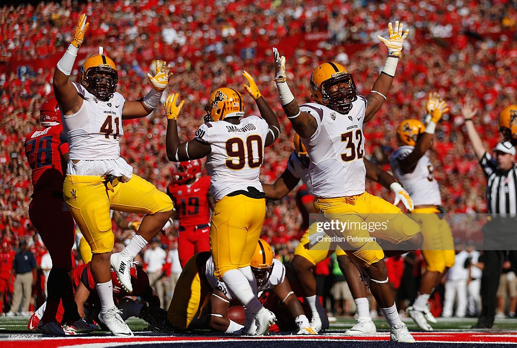 Linebacker Viliami Latu #41, defensive lineman Tashon Smallwood #90 and linebacker Antonio Longino #32 of the Arizona State Sun Devils celebrate after Demetrius Cherry (not pictured) scored on a fumble recovery in the first quarter during the Territorial Cup college football game against the Arizona Wildcats at Arizona Stadium on November 28, 2014 in Tucson, Arizona.