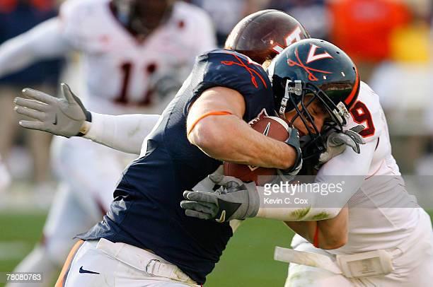 Linebacker Vince Hall of the Virginia Tech Hokies tackles fullback Josh Zidenberg of the Virginia Cavaliers during the second half at Scott Stadium...