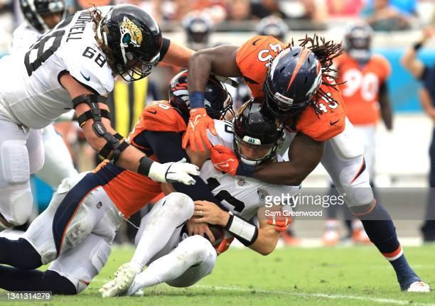 Linebacker Von Miller and linebacker Alexander Johnson of the Denver Broncos tackle quarterback Trevor Lawrence of the Jacksonville Jaguars during...