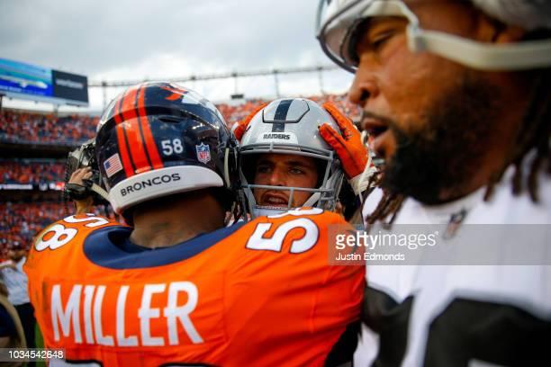 Linebacker Von Miller of the Denver Broncos greets quarterback Derek Carr of the Oakland Raiders on the field after a 2019 Denver Broncos win at...