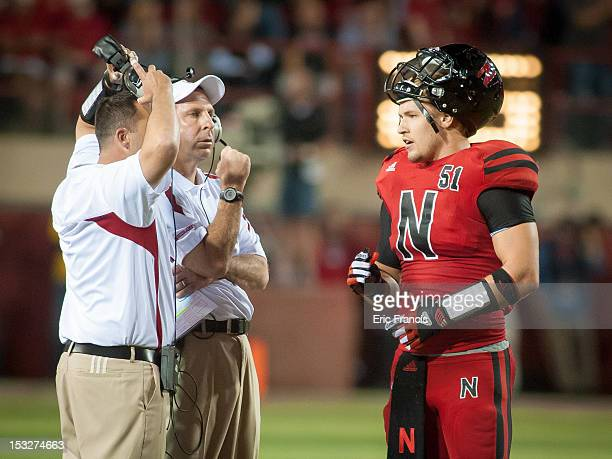 Linebacker Will Compton of the Nebraska Cornhuskers talks with defensive coaches during a time out during their game against the Wisconsin Badgers at...