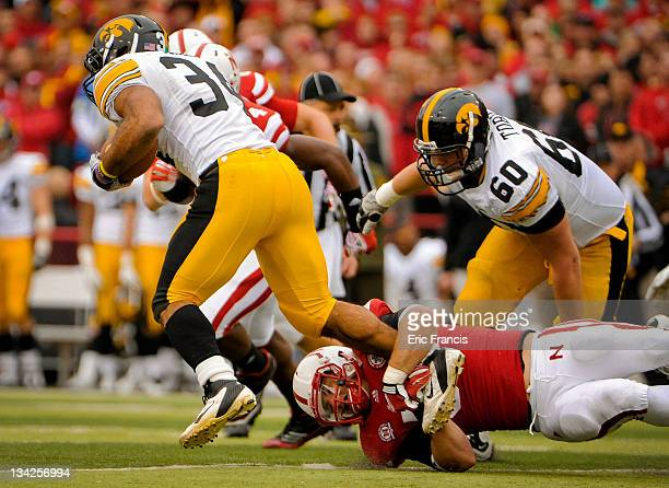 Linebacker Will Compton of the Nebraska Cornhuskers trips up running back Marcus Coker of the Iowa Hawkeyes during their game at Memorial Stadium...