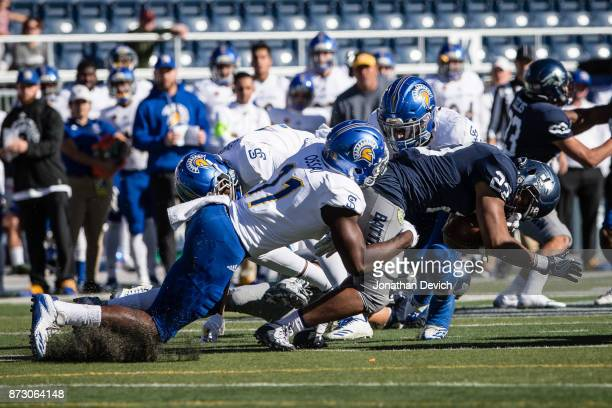 Linebacker William Ossai of the San Jose State Spartans tackles running back Kelton Moore of the Nevada Wolf Pack at Mackay Stadium on November 11...