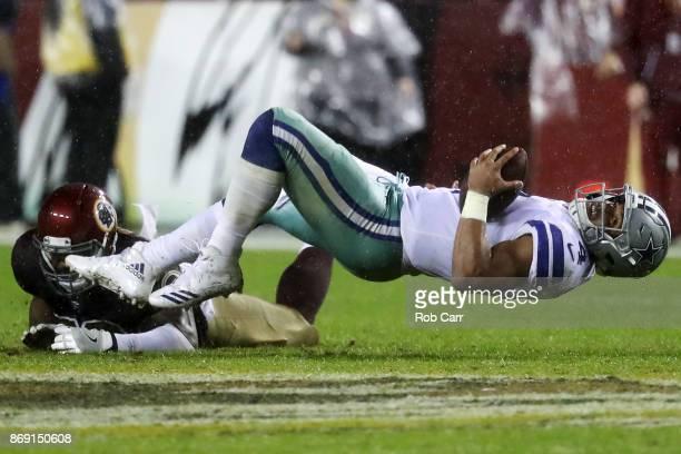 Linebacker Zach Brown of the Washington Redskins tackles quarterback Dak Prescott of the Dallas Cowboys at FedEx Field on October 29 2017 in Landover...