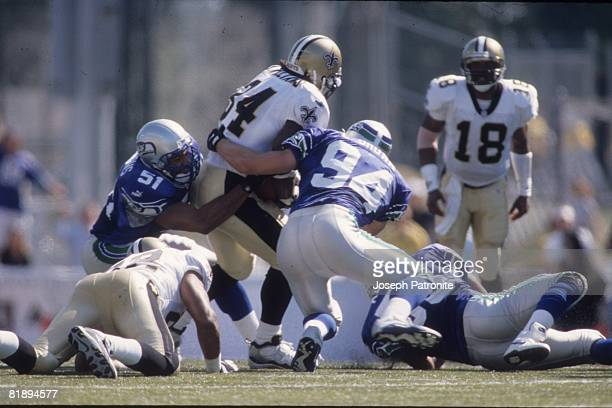 Linebackers Anthony Simmons and Chad Brown of the Seattle Seahawks stop running back Ricky Willliams of the New Orleans Saints at Husky Stadium in...