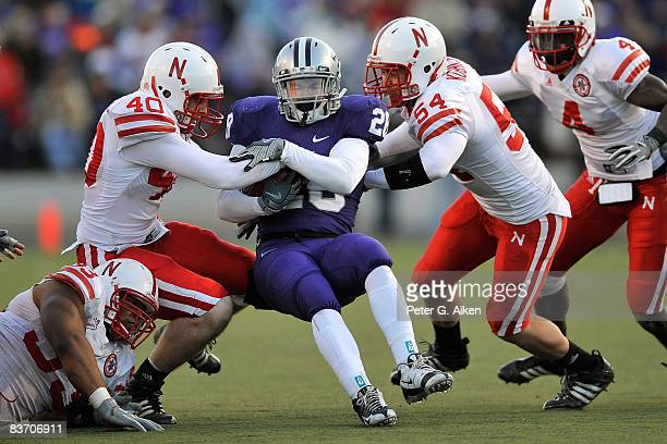 Linebackers Blake Lawrence and Colton Koehler of the Nebraska Cornhuskers tackle running back Logan Dold of the Kansas State Wildcats for no gain...