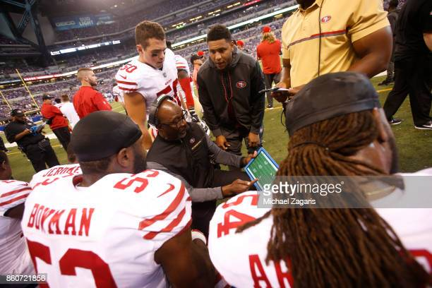 Linebackers Coach Johnny Holland of the San Francisco 49ers talks with Brock Coyle, NaVorro Bowman and Ray-Ray Armstrong on the sideline during the...